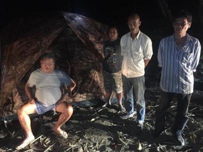 """Premchai Karnasuta, far left, sits in the campsite where he was found with the remains of a leopard, panther and other wildlife Monday in the Thungyai Naresuan Wildlife Sanctuary in Kanchanaburi province"" (Photo: khaosodenglish.com)."