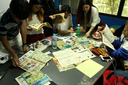 "CommDe students flipping through 1940s-1970s issues of the ""Spirou"" magazine (with some Spirou/Marsupilami stories, Jijé's Jerry Pring pages, and ""Le Trombone Illustré"" supplement)."