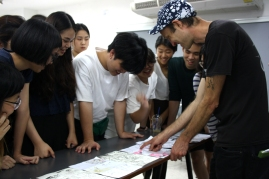 Collective reading of the resulting collaborative comics loop: student Uang explains her plot to Anders and her classmates.