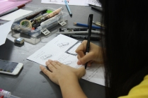 "Getting serious, or trying. Student Kade working on her ""I Almost Died!"" constrained comics assignment."